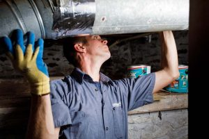 service technician installing heating ductwork